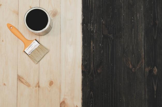 Pennello vicino al barattolo sdraiato su fondo in legno. la superficie è mezza colorata di nero. vista dall'alto.
