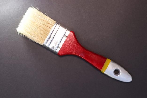 Pennello. pittura superficiale. strumento di lavoro. sfondo sfumato nero. copia spazio per il testo.