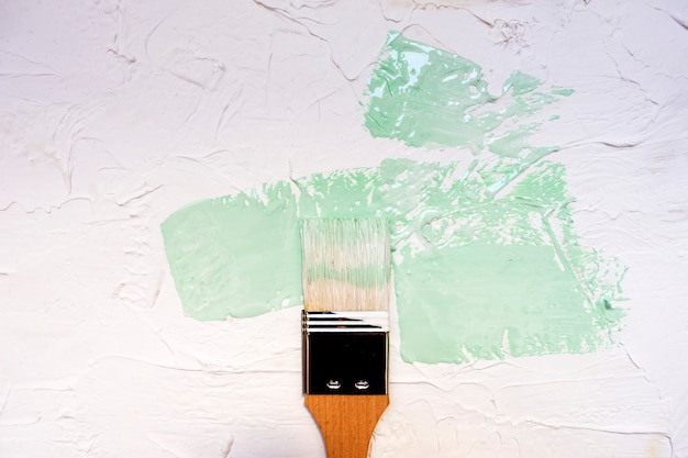 Pennello con la vernice di colore sul fondo bianco della parete