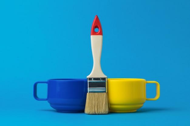 Pennello, tazza gialla e blu su sfondo blu. la tendenza del colore.