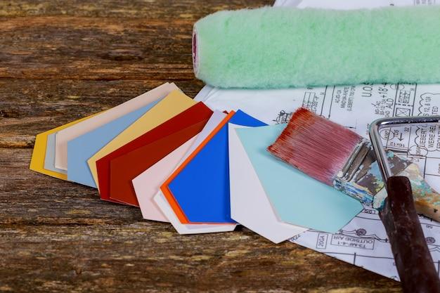 Pennelli, rullo di vernice su disegni di carta progetto architettonico
