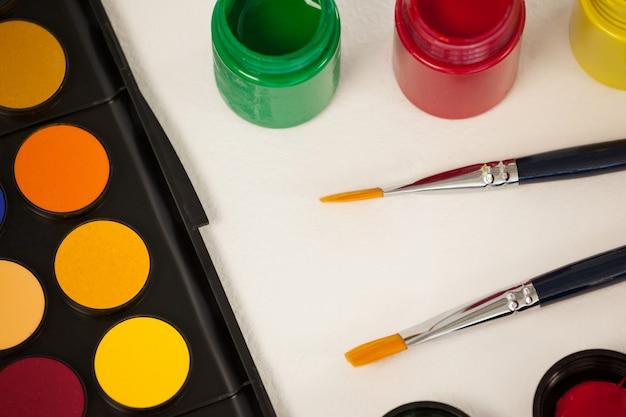 Pennelli, colori ad acquerello e tavolozza di acquerelli su superficie bianca