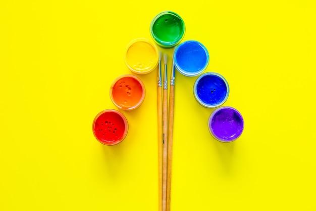 I barattoli di vernice stanno in un angolo, i colori sono visualizzati nell'ordine dell'arcobaleno sotto di loro sono pa...
