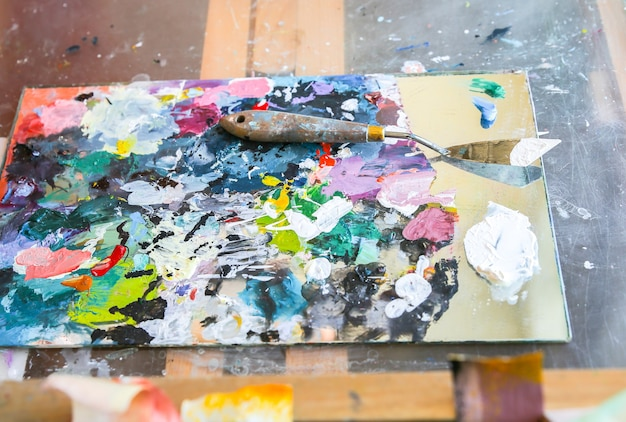 Tavolozza di vernice. vero studio di lavoro del pittore. l'uomo sta creando un'immagine. concetto di artista. atmosfera creativa.