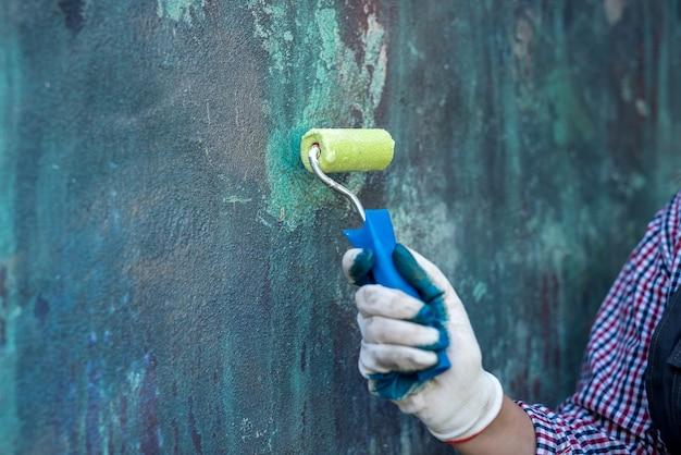 Rullo di vernice in mano femminile vicino alla parete colorata