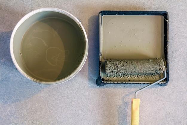 Rullo di vernice nel vassoio con la latta di vernice sul pavimento di cemento.