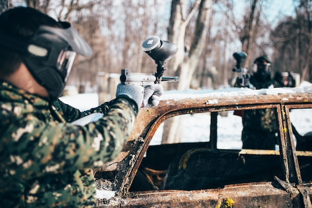 Battaglia di paintball, i giocatori sparano a causa di un'auto bruciata nella foresta invernale, paintball. sport estremo, gioco militare
