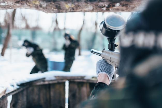 Giocatore di paintball che spara alla squadra nemica, battaglia nella foresta invernale. gioco militare estremo
