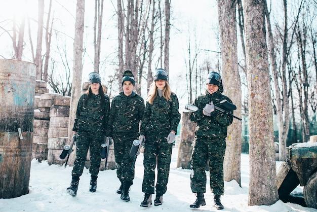 Giocatori di paintball in uniforme e maschere dopo la battaglia nella foresta invernale. gioco di sport estremi