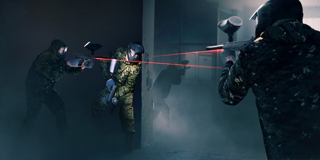 Squadra di paintball in battaglia, pistole con mirino laser. gioco di sport estremi, giocatori con maschere protettive e camuffamento tengono l'arma in mano