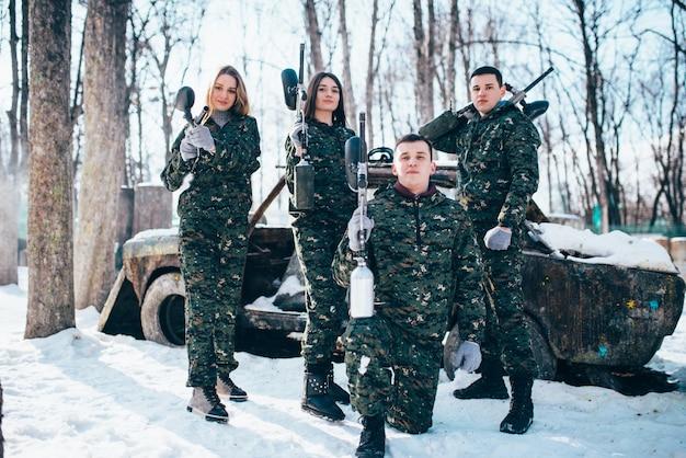 La squadra di paintball posa con le pistole dell'indicatore