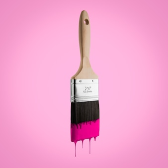 Pennello caricato con colore rosa che gocciola dalle setole isolato su sfondo rosa.