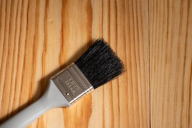 Pennello posizionato su una superficie di legno e spazio per il testo a lato