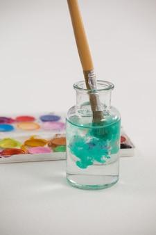 Pennello con vernice blu immerso in un barattolo riempito d'acqua contro la superficie bianca