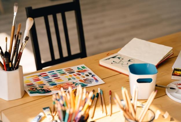 Pennello con tubi di colori ad olio e matite colorate. strumenti di arte e artigianato,inchiostro,tavolo in legno.pittura per artisti contemporanei.articoli per la creatività degli adulti.disegno ad acquerello.foto moderna d'atmosfera