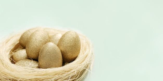 Uova di pasqua dipinte color oro in nido di paglia su verde chiaro. vacanze di pasqua di primavera