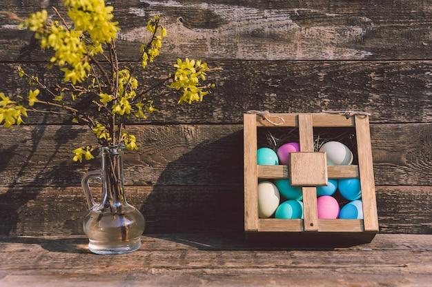 Uova dipinte in una scatola su un tavolo con un vaso di fiori. sullo sfondo di vecchie schede. concetto sul tema della pasqua.