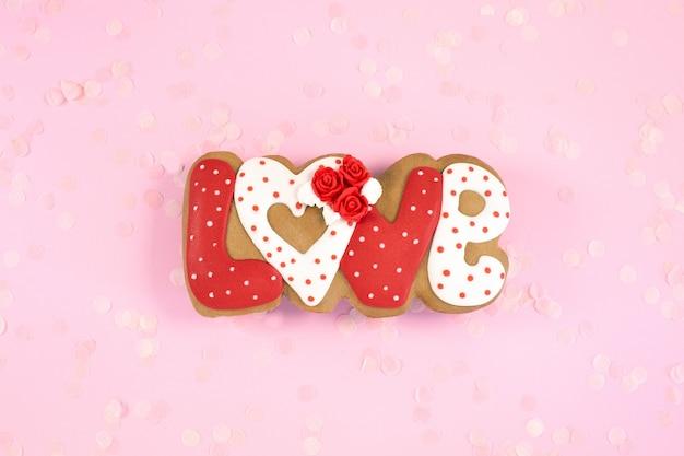 Biscotti di panpepato dipinti a forma di parola amore su una scrivania rosa. concetto di amore romanticismo vista dall'alto. copia spazio
