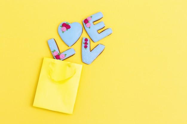 Pan di zenzero dipinto a forma di parola amore sparsi dal sacchetto di carta