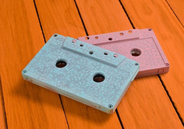 Dipinto in una cassetta audio di colore pastello blu rosa su uno sfondo di legno arancione. tecnologia audio retrò vista dall'alto.