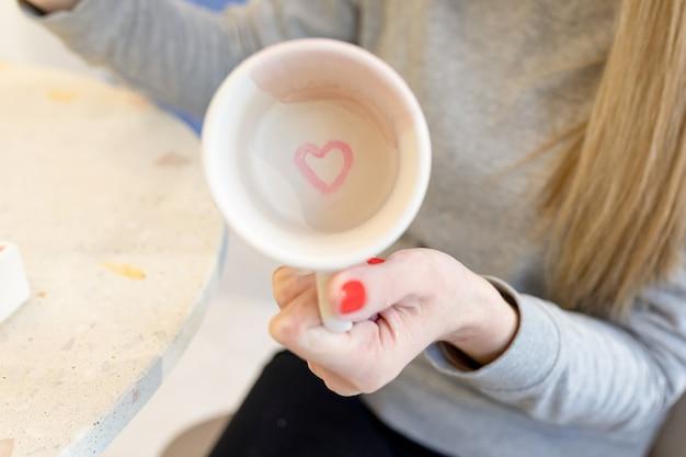 Cuore rosa dipinto sul fondo della tazza una donna mostra i risultati del suo lavoro