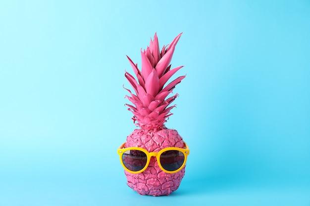 Ananas rosa dipinto con gli occhiali da sole su fondo blu