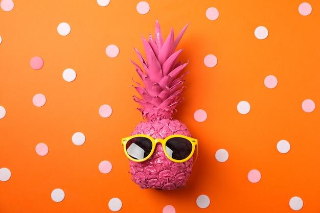 Ananas rosa dipinto con gli occhiali da sole su fondo arancio decorato
