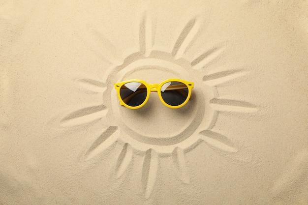 Sole dipinto e occhiali da sole gialli su sabbia di mare