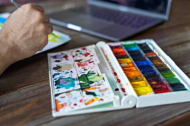 Artista pittore utilizzando colori ad acquerello nella parte anteriore del computer portatile