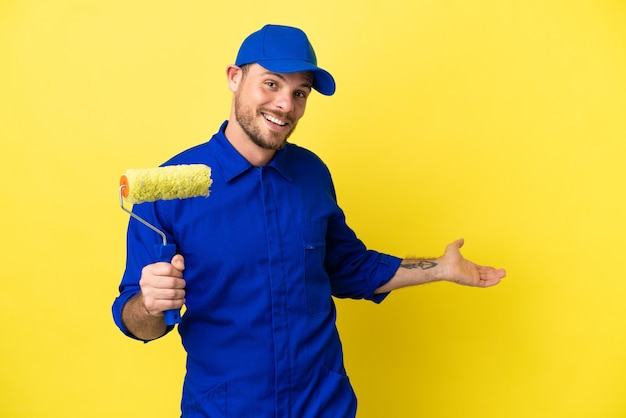 Pittore brasiliano uomo isolato su sfondo giallo che estende le mani di lato per invitare a venire