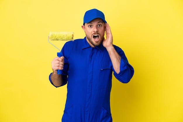 Pittore brasiliano uomo isolato su sfondo giallo con espressione facciale sorpresa e scioccata