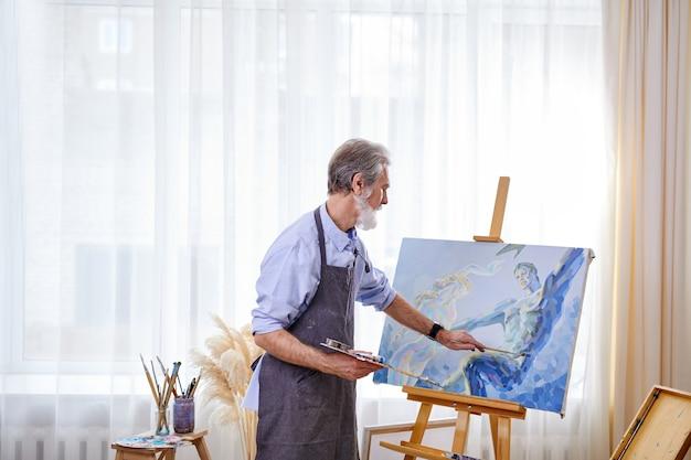 Pittore che crea capolavori, uomo anziano che lavora su tela, usando colori, pennelli, cavalletto e altri strumenti