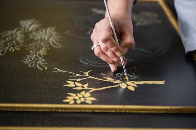 Il decoratore del pittore disegna un modello di albero e foglie