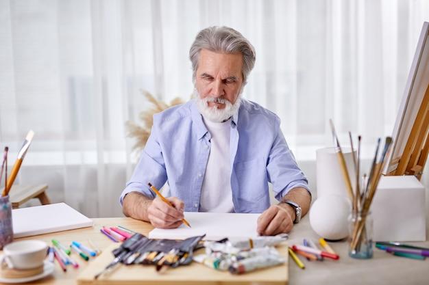 Il pittore disegna a casa usando la matita, concentrato sul lavoro, indossa una camicia blu.