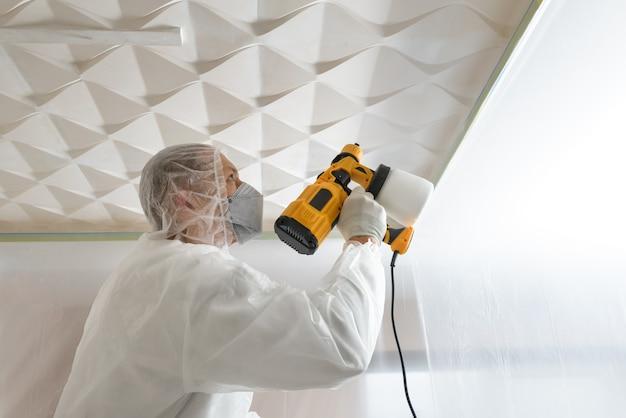 Il pittore dipinge un soffitto tridimensionale con una pistola a spruzzo.