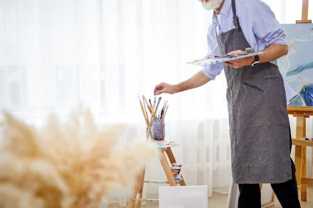 Uomo del pittore in grembiule che prende il pennello dalla latta, nella stanza leggera. artista ritagliata che tiene la tavolozza dei colori nelle mani