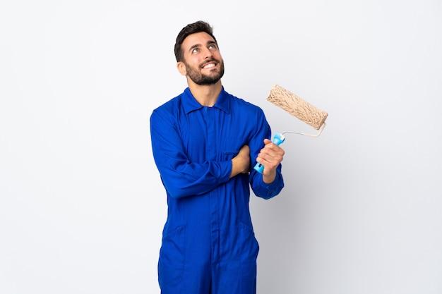 Uomo del pittore che giudica un rullo di pittura isolato sulla parete bianca che cerca mentre sorridendo