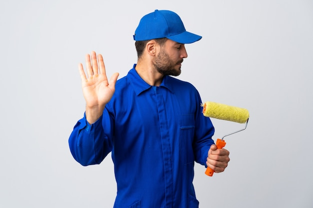 Uomo del pittore che tiene un rullo di vernice isolato sul muro bianco che fa il gesto di arresto e deluso