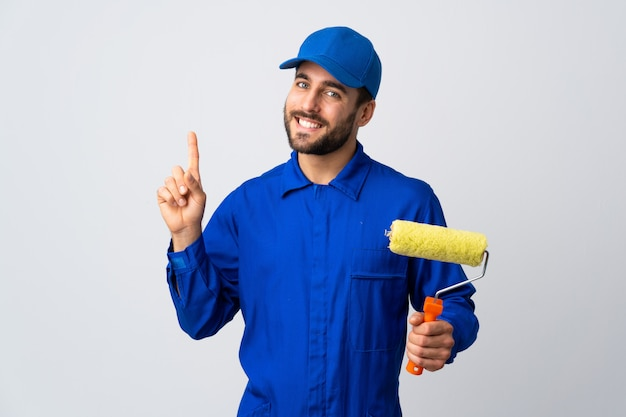 Uomo del pittore che giudica un rullo di pittura isolato sulla rappresentazione bianca della parete e che solleva un dito nel segno del meglio