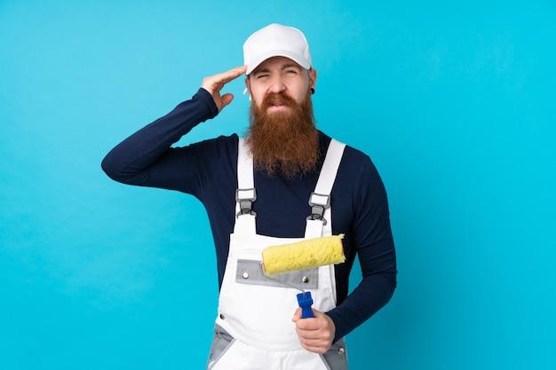 Uomo del pittore con la barba lunga sopra la parete blu isolata infelice e frustrato con qualcosa. espressione facciale negativa