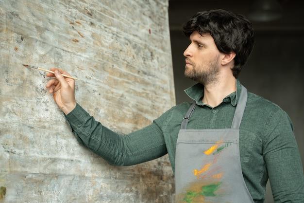 Uomo del pittore che lavora in una tela a olio astratta moderna nel suo studio