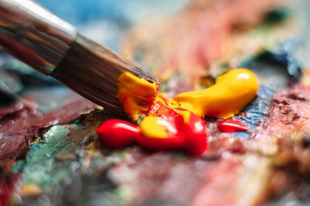Pittore che mescola pittura ad olio sulla tavolozza con il pennello