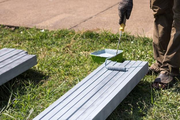 Pittore pittura metallo. lavoratore tenendo il rullo e immergendo nel secchio di vernice