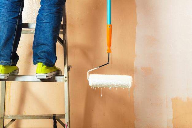 Pittore che dipinge le pareti bianche in casa