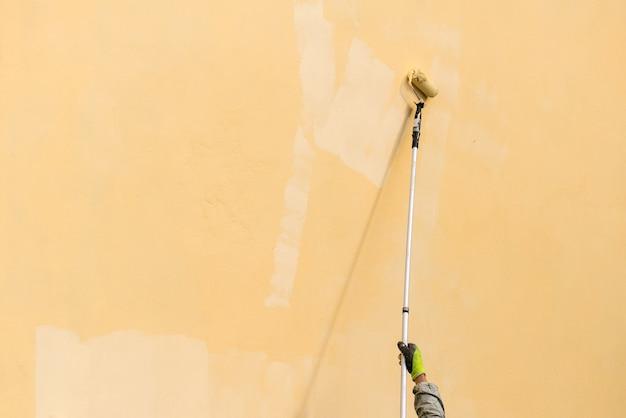 Il pittore dipinge la parete esterna dell'edificio con un rullo. rullo con bastone lungo che dipinge manualmente l'edificio con vernice gialla