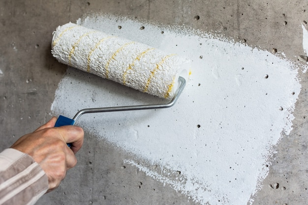 Un pittore dipinge un muro di cemento con vernice bianca, una mano maschile con un rullo di vernice per dipingere un muro