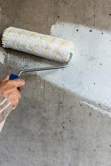 Un pittore dipinge un muro di cemento con vernice bianca