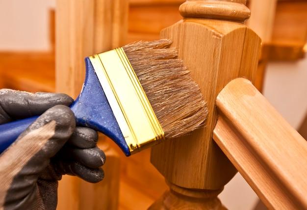 Il pittore dipinge una tavola di legno di vernice a pennello