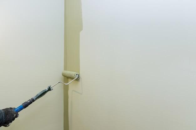 Appartamento di pittura, ristrutturazione con muro dipinto a mano maschile con rullo di vernice