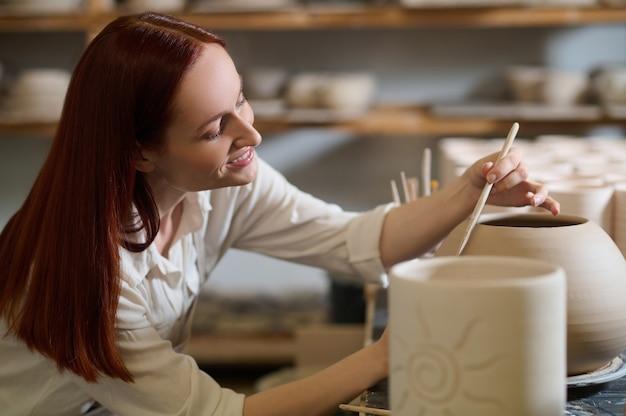 La pittura. una simpatica vasaio femmina che sembra coinvolta mentre dipinge il vaso
